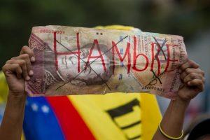 """CAR01. CARACAS (VENEZUELA), 08/08/2015.- Una persona sostiene en su mano un billete de 100 bolívares fuertes falso, con la para """"hambre"""" durante una manifestación hoy, sábado 8 de agosto de 2015, en la ciudad de Caracas (Venezuela). La alianza opositora venezolana Mesa de la Unidad Democrática (MUD) admitió que fue escasa la asistencia a la manifestación que convocó para hoy en Caracas, pero subrayó que ello no pone en dudas el triunfo que prevé en los comicios de diciembre. La convocatoria a marchar por todas las capitales de los 24 estados del país, y por zonas del centro-este de Caracas, """"contra el hambre, contra el hampa por la libertad, por la unidad"""", finalmente reunió a unas pocas decenas de personas en una sola calle de la capital venezolana. EFE/MIGUEL GUTIERREZ"""