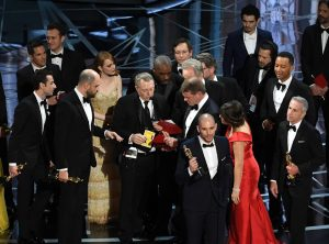 HOLLYWOOD, CA - FEBRUARY 26: 'La La Land' producer Fred Berger (R) speaks at the microphone as production staff consult behind him regarding a presentation error of the Best Picture award (later awarded to 'Moonlight') onstage during the 89th Annual Academy Awards at Hollywood & Highland Center on February 26, 2017 in Hollywood, California. Kevin Winter/Getty Images/AFP