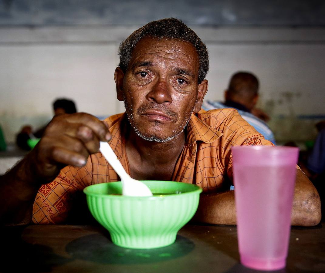 """Carlos Son, 60, poses for a picture at the Mother Teresa of Calcutta eating center in Caracas March 21, 2014. Carlos lives alone and used to work as plumber. He has been having meals at the eating center for over one year, because he is unemployed and has no money. The Mother Teresa of Calcutta eating center, located in a back-street of Caracas, is frequented by people who are unemployed and homeless, as well as those who work but are unable to make ends meet. Shortages of basic products have become the norm in Venezuela over the last year and workers at soup kitchens for the homeless and hungry face an ever-more difficult task in finding the staple foods they need to provide a free hot daily meal. Opponents of President Nicolas Maduro's government say the queues are a national embarrassment and symbol of failed socialist economics similar to the old Soviet Union. But officials say businessmen are deliberately hoarding products as part of an """"economic war"""" against him. Picture taken March 21, 2014. REUTERS/Carlos Garcia Rawlins (VENEZUELA - Tags: POLITICS SOCIETY FOOD)ATTENTION EDITORS: PICTURE 23 OF 27 FOR PACKAGE 'HUNGRY IN CARACAS'TO FIND ALL IMAGES SEARCH 'BOLIVAR CARACAS'"""