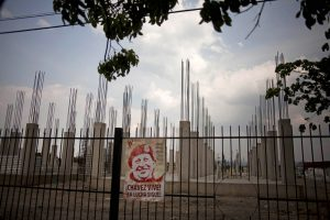 Una foto de Hugo Chávez cuelga de un cerco que rodea un proyecto de viviendas que no ha sido completado en Valencia, Venezuela, el 8 de abril del 2013. Las promesas incumplidas durante el gobierno de Chávez, la pobreza, apagones, la violencia, la inflación, la corrupción oficial y la escasez de alimentos podrían incidir en las elecciones presidenciales del domingo. (AP Photo/Ramón Espinosa).