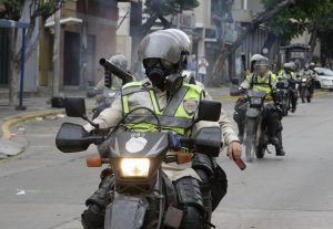 Riot police ride their motorbikes during a march against President Nicolas Maduro, in Caracas on May 1, 2017. Security forces in riot vans blocked off central Caracas Monday as Venezuela braced for pro- and anti-government May Day protests one month after a wave of deadly political unrest erupted. / AFP PHOTO / FEDERICO PARRA