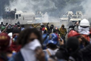 Opposition activists, equipped with helmets, gas masks, makeshift shields and barricaded behind debris, face charging riot police during a protest against Venezuelan President Nicolas Maduro, in Caracas on May 3, 2017. Venezuela's angry opposition rallied Wednesday vowing huge street protests against President Nicolas Maduro's plan to rewrite the constitution and accusing him of dodging elections to cling to power despite deadly unrest. / AFP PHOTO / JUAN BARRETO