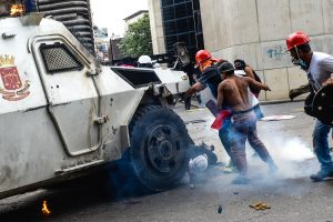 A Venezuelan National Guard riot control vehicle runs over an opposition demonstrator during a protest against Venezuelan President Nicolas Maduro, in Caracas on May 3, 2017. Venezuelan police fired tear gas and hooded protesters hurled Molotov cocktails as thousands rallied Wednesday in anger at President Nicolas Maduro's plan to rewrite the constitution. At least one protester caught fire and two opposition lawmakers were among various people injured, AFP reporters at the scene said. / AFP PHOTO / FEDERICO PARRA