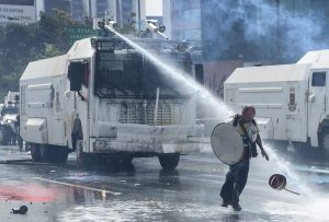 """An opposition activist is hit at close quarters by the jet from a riot police water cannon during a protest against President Nicolas Maduro in Caracas, on May 10, 2017. Venezuelan protesters hit the streets on Wednesday armed with """"Poopootov cocktails,"""" jars filled with excrement which they vowed to hurl at police as a wave of anti-government demonstrations turned dirty. / AFP PHOTO / JUAN BARRETO"""