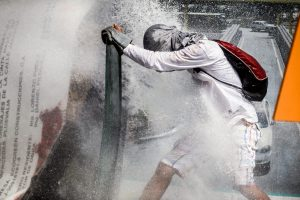 An opposition activist holds a makeshift shield to protect himself from the jet of a riot police water cannon during a protest against President Nicolas Maduro in Caracas, on May 26, 2017. Both the Venezuelan government and the opposition admit that violent protests that have gripped the country for nearly two months are out of control -- and analysts warn they could be a double-edged sword that might trigger even more unrest. / AFP PHOTO / FEDERICO PARRA