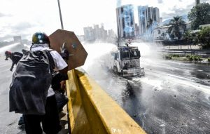 Opposition activists clash with the police as they block the Francisco Fajardo highway in Caracas during a demonstration against President Nicolas Maduro's government on May 29, 2017.  Demonstrations that got underway in late March have claimed the lives of 59 people, as opposition leaders seek to ramp up pressure on Venezuela's leftist president, whose already-low popularity has cratered amid ongoing shortages of food and medicines, among other economic woes. / AFP PHOTO / Juan BARRETO