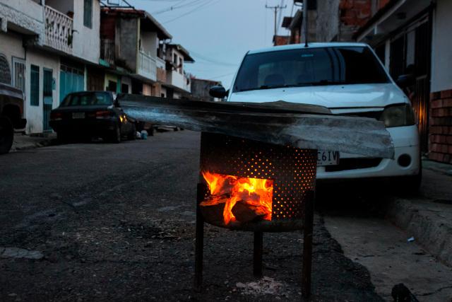 """Fotografía de archivo fechada el 30 de marzo del 2020 donde se observa un fogón prendido con leña para poder cocinar, en San Cristóbal (Venezuela). """"No son sanciones para el Gobierno, son sanciones para el Estado venezolano. Aquí están sancionando a todo el mundo, nos afecta a todos"""". José Colmenares lo tiene claro. Las multas impuestas por Estados Unidos, la Unión Europea y otros países a Venezuela afectan a todos, especialmente al pueblo, el último eslabón de una cadena rota desde hace tiempo. EFE/JOHNNY PARRA"""