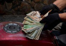 Un hombre muestra un fajo de bolívares y dólares previo a comprar gasolina para su moto en una estación de servicio, en Caracas (Venezuela). EFE/RAYNER PEÑA R